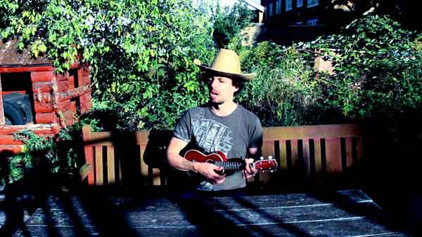 Man playing ukulele in the garden with a straw hat on