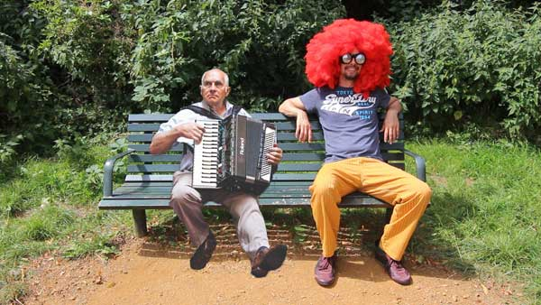 Crazy man with big red hair sat next to an old accordionist on a bench