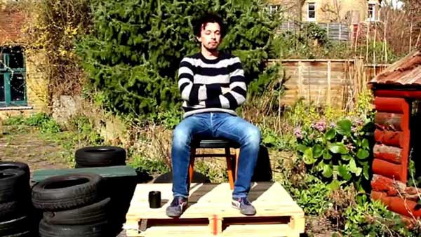 Man sitting on some wooden palettes