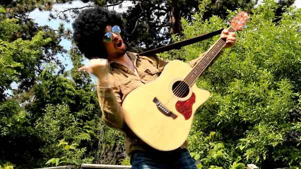 Acoustic guitarist outside with an afro wig