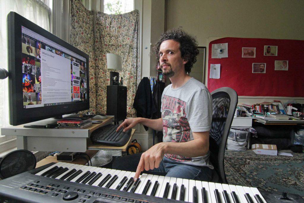 Elliot Mason writing his blog at home